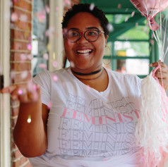 Headshot of a black woman smiling while tossing up pink confetti in Raleigh, NC