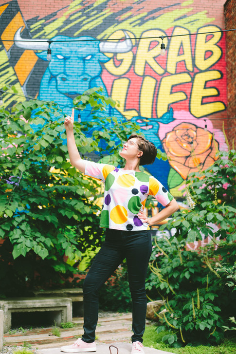 """Portrait of woman in downtown Durham pointing up to a mural that says """"Grab life"""" with an image of the durham Bull."""