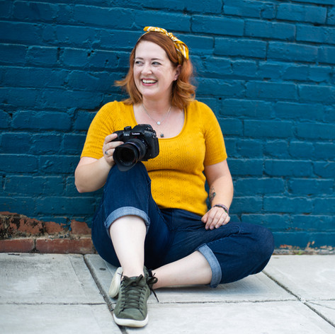 Headshot of Woman with bright red hair, yellow top, and pants holding a camera in front of a Blue wall