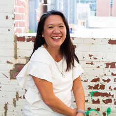 Headshot of smiling Asian woman wearing a white blouse in front of the downtown Raleigh, NC train station