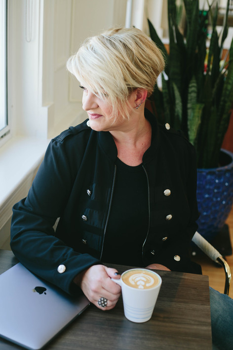 Brand Photography for a woman with bright blonde hair with her laptop and a latte in downtown Raleigh, NC