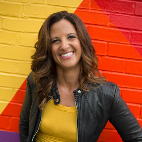 Headshot of woman in leather jacket, yellow top, and patterned skirt in front of a brightly colored geometric mural in Raleigh, NC