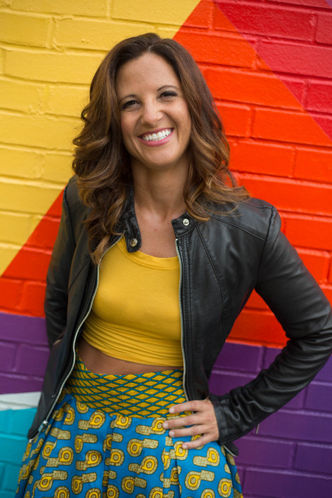 Headshot of woman in front of a bright geometric mural in Raleigh, NC