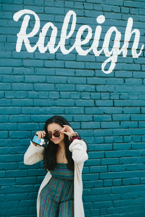 Headshot of College student with sunglasses in front of Raleigh mural in Raleigh, North Carolina