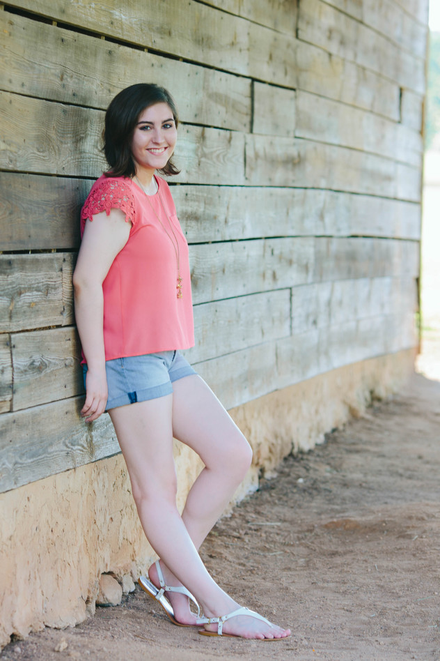 High School Senior portrait of girl in Wake Forest, NC leaning on barn wall