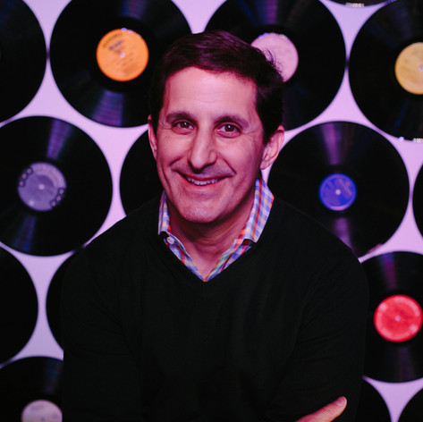 Headshot of man in a navy sweater in front of a wall of records at Imurj in Downtown Raleigh, North Carolina