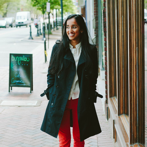 Portrait of Indian woman in a black trench coat, red pants, and nude heels in Downtown Durham, North Carolina