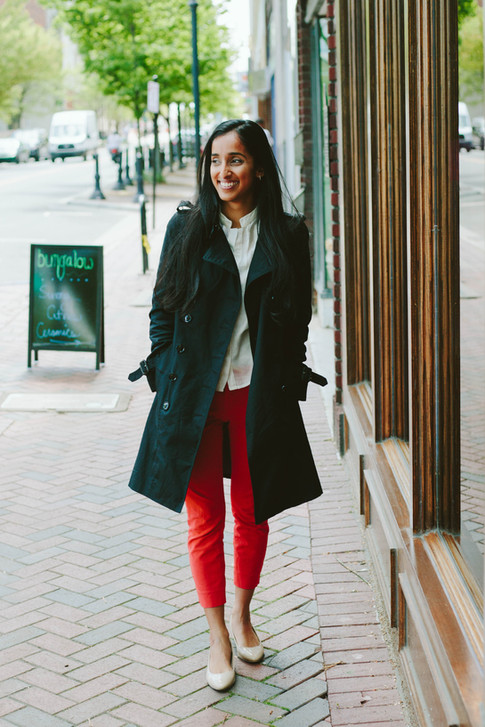 Headshot of indian woman with black blazer and red pants in downtown Durham, NC