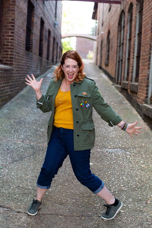 Brand Photography for woman playfully doing Jazz hands in Downtown Raleigh, NC