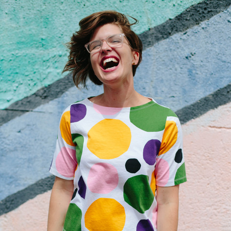 Headshot of woman with brown short hair wearing a polka dotted shirt laughing while standing in front of a wall with pastel stripes in Durham, NC