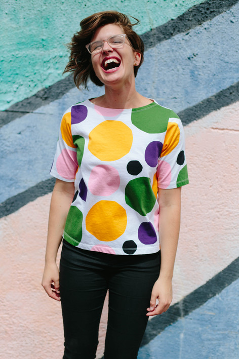 Headshot of woman in polka dotted shirt laughing in front of a mural in downtown Durham, NC
