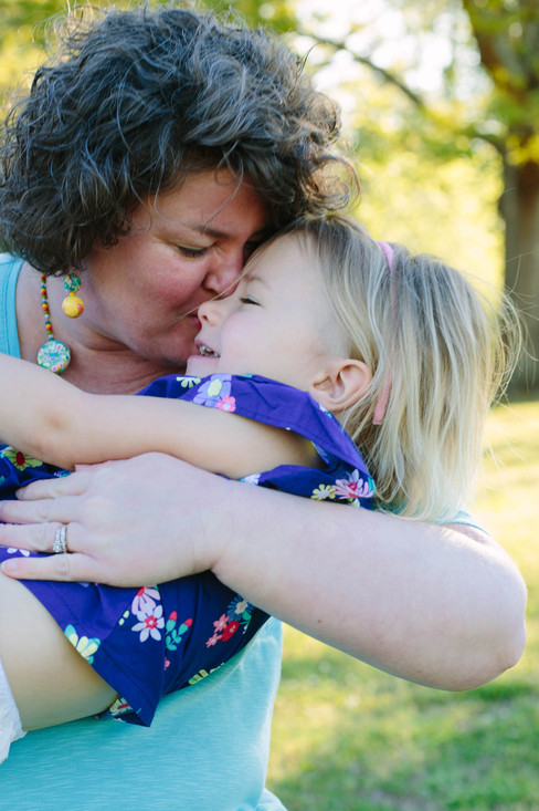 Mother daughter portrait in Wake Forest, NC where mom is kissing her daughter