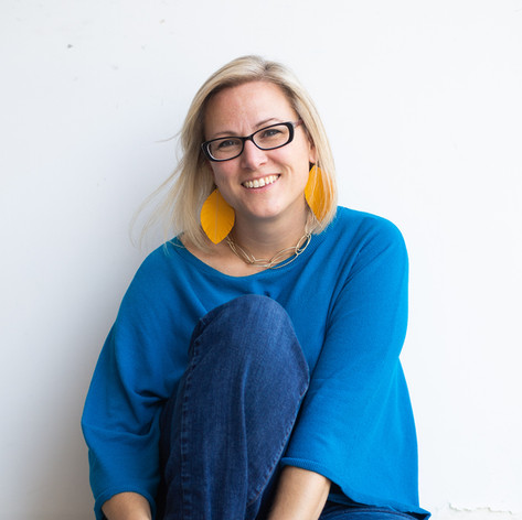 Headshot of blonde hair woman in blue top, jeans, and yellow earrings in Raleigh, North Carolina