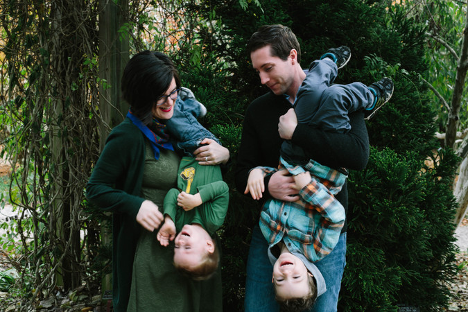 Family portrait at a park in Raleigh NC with two parents tickling their kiddos