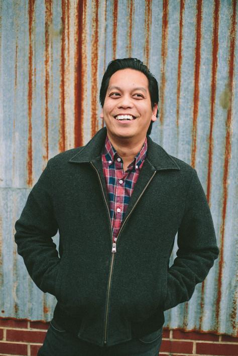 Headshot of man with dark brown hair, a jacket, and button down shirt in Durham, North Carolina