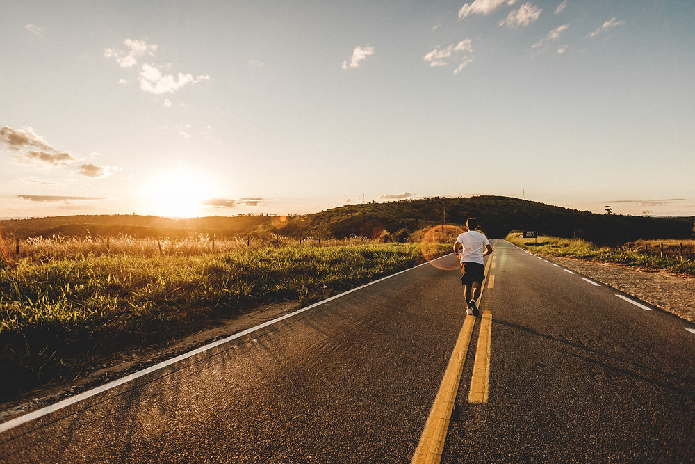 Man running on open road during the sunset