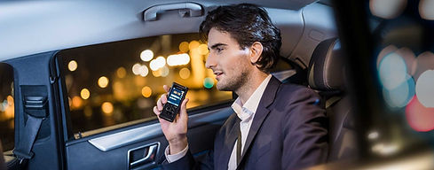 man in a car dictating into an Olympus recording device
