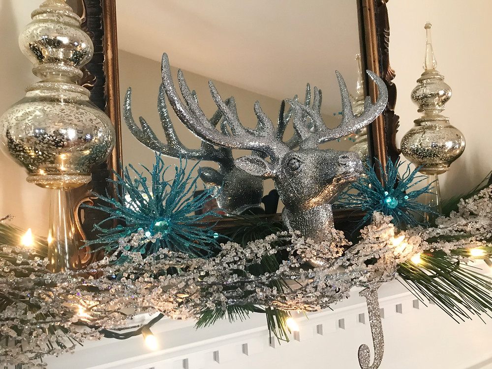 Holiday Decor with silver reindeer mantle piece with teal and gold holiday accents.
