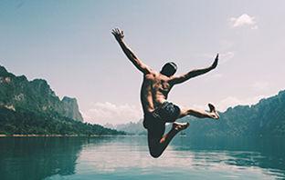 man-jumping-with-joy-by-lake.jpg