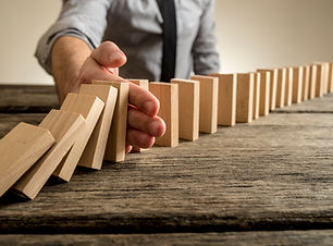 man-stopping-domino-effect-on-wooden-tab