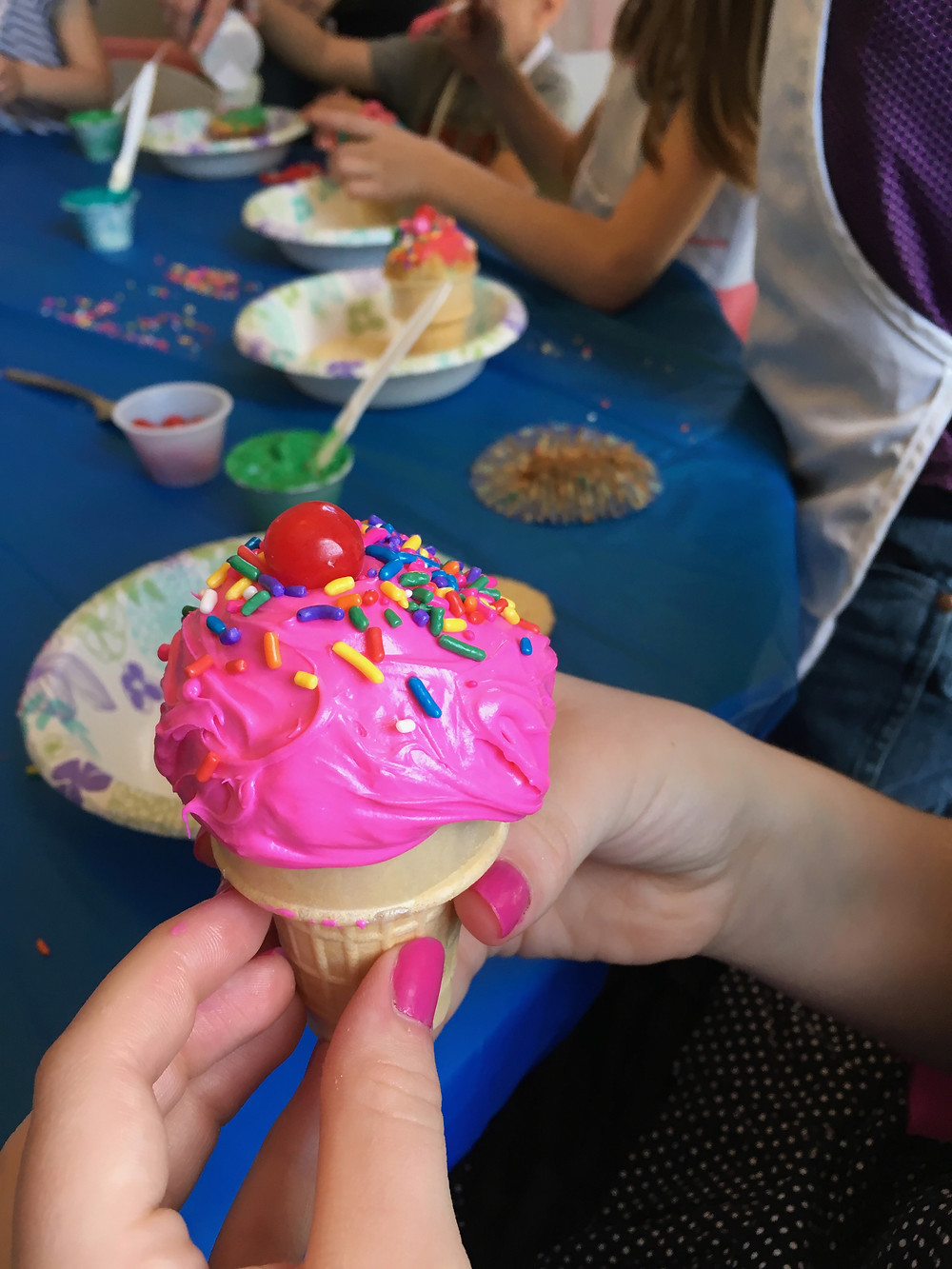 Manicured dainty fingers hold a sweet celebration specialty cupcake cone at a baking party!