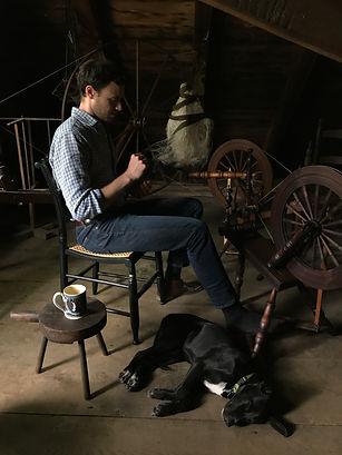 Justin Squizzero handspinning flax in the Burroughs Garret.