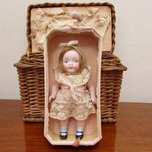 All bisque Painted Eye Googly Doll in Wicker Basket with Costumes