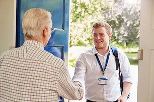 Senior man greeting male care worker mak