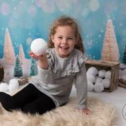 enfant en studio qui tient balle de neige