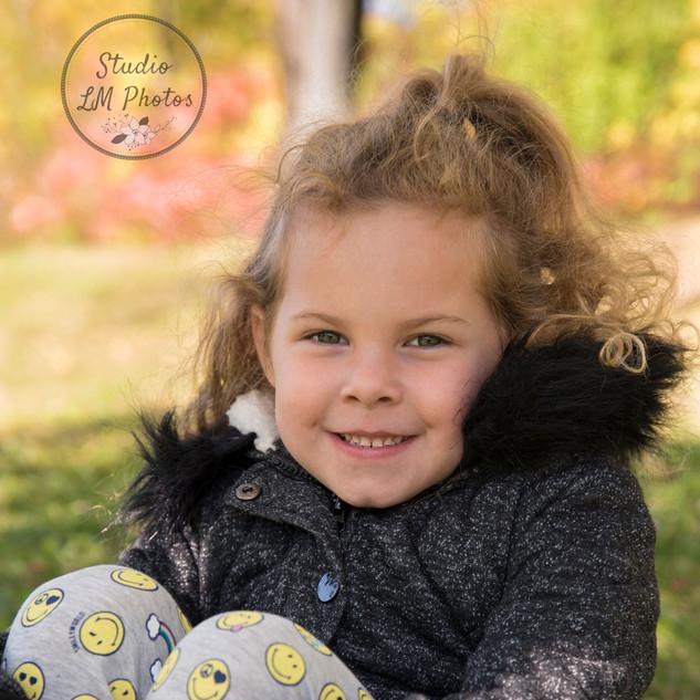 petite fille assise dans un décor d'automne