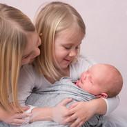 deux petites soeurs avec nouveau-né