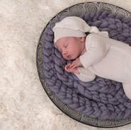 nouveau-né couché sur laine mauve dans un décor blanc