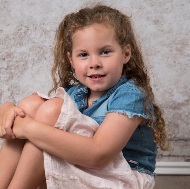 portrait d'une petite fille assise devant un fond abstrait