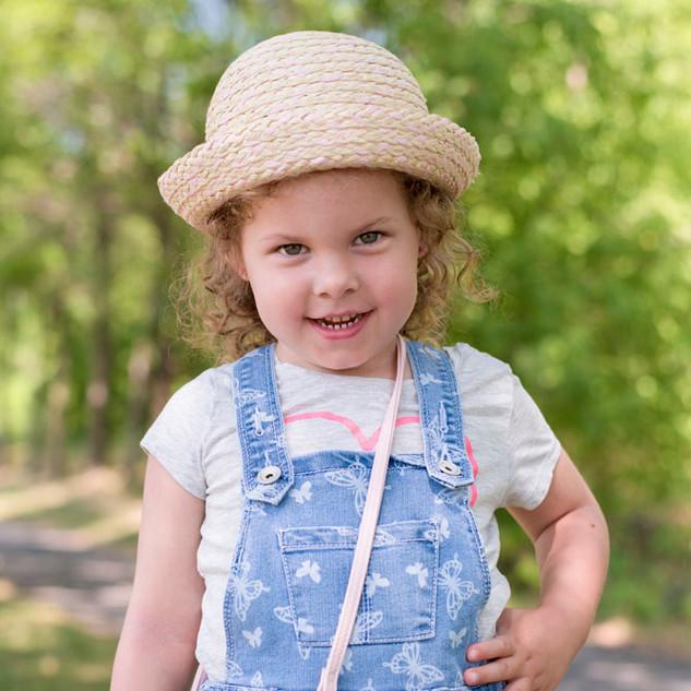 petite fille coquette portant un chapeau