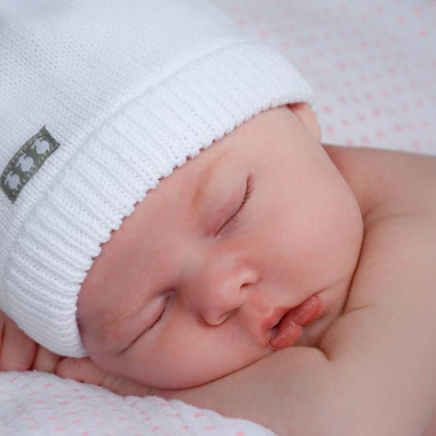 nouveau-né endormi avec chapeau blanc