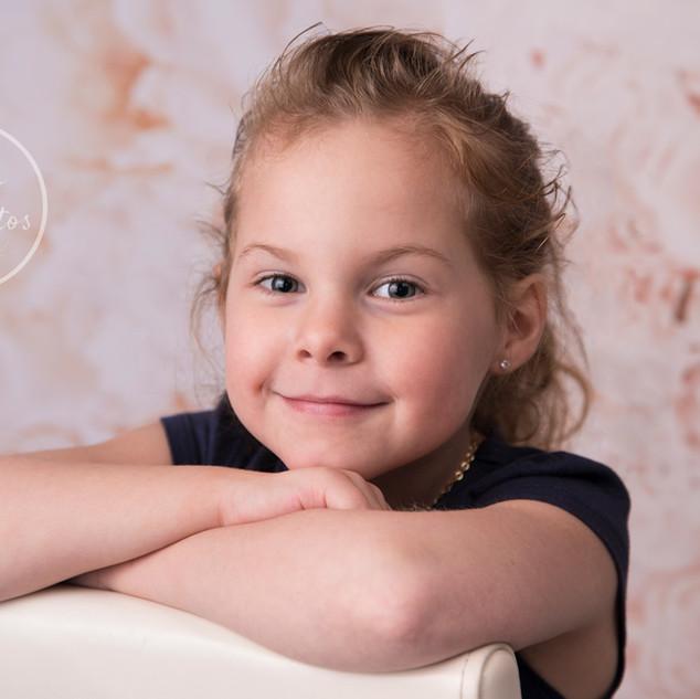 petite fille assise les bras croisés sur une chaise