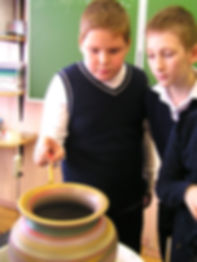 На гончарном мастер-классе дети расписывают вазу учителю