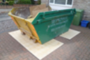 Skip placed on boards to protect driveway