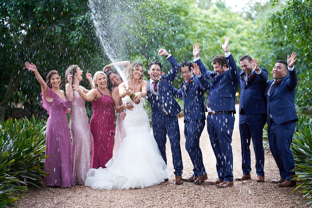 Photo of the bride spraying champagne while bridesmaids and groomsmen are behind her