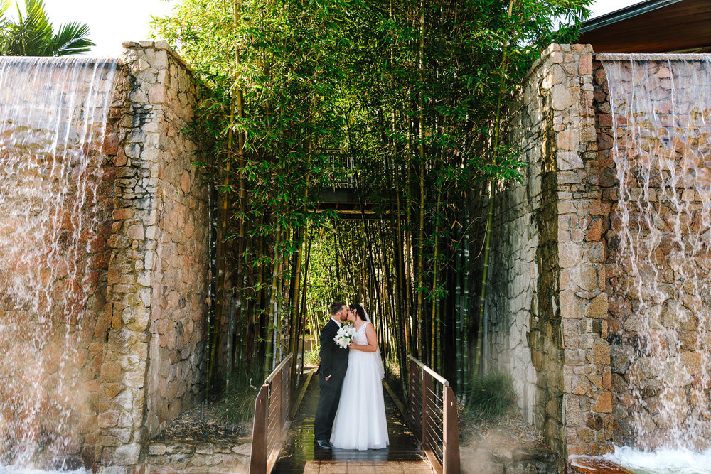 Bride and Groom photo kissing with a bamboo background and an old buidling