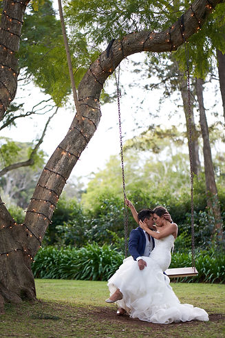 Bride sitting on the groom's lap on a swing