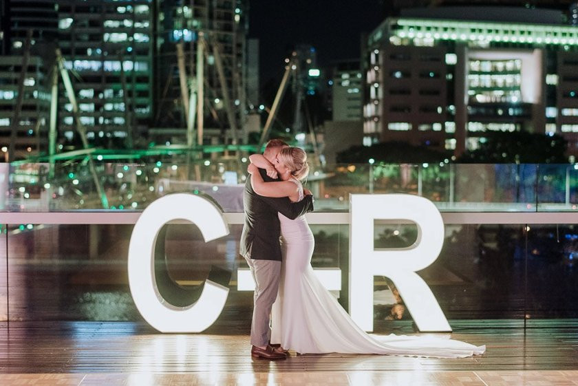 Newly weds hugging each other with a sign background