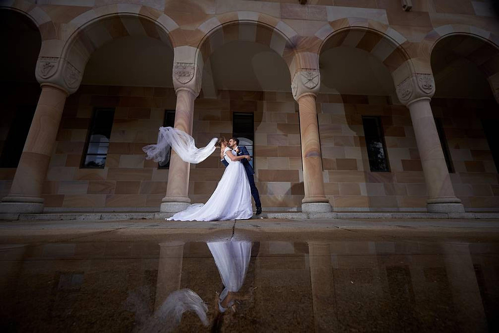Photo of newly weds with pillar background and water reflection