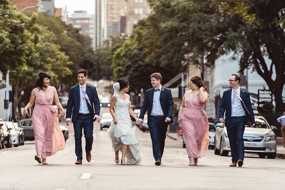 Photo of newly weds, bridesmaids and the best man walking on the street