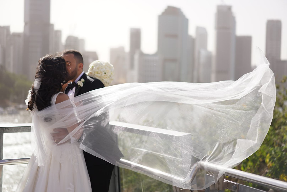 Bride and Groom kissing with a skyline background