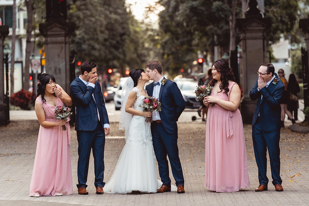 Newly weds kissing while bridesmaids and groomsmen are watching