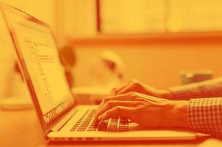 Persona escribe en computador desenfocado