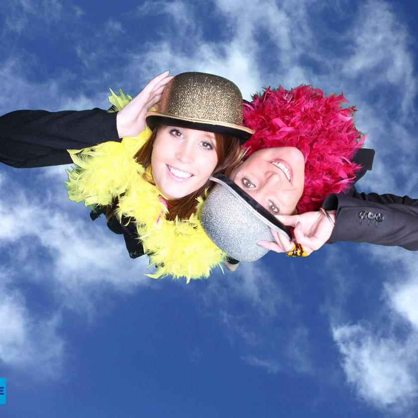 Studio photo l'Œil du Plafond sur ciel bleu. Deux filles avec chapeaux et boas souriantess
