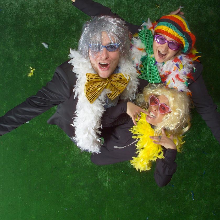 studio photo de l'Œil du Plafond  sur fond gazon. trois personnes avec perruques, lunettes et boas esprit de fête