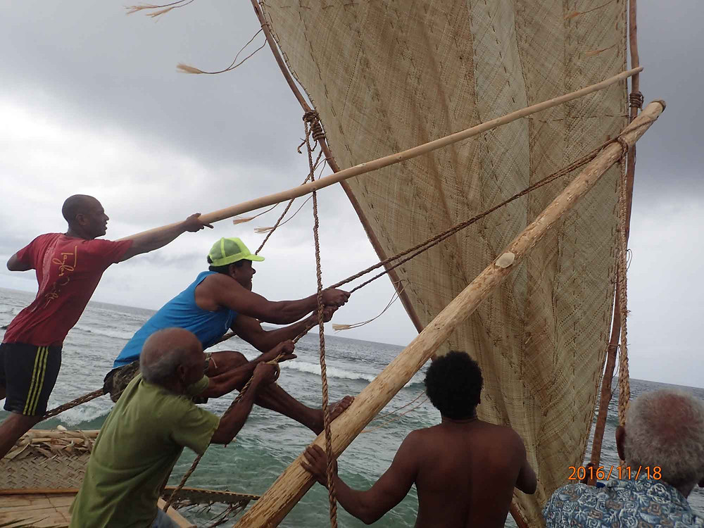 Ambrose pulls halyard to secure windward boom to mast.